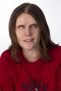 Meine Wenigkeit an einem höheren Pult in einem Fotostudio stehend. Ich habe mittellanges, braunes Haar und trage ein rotes Oberteil.
